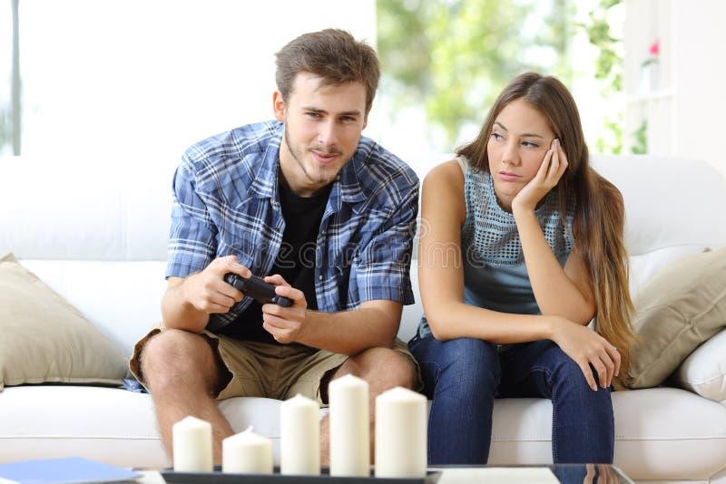 Mens het spelen videospelletjes en meisje bored naast stock fotografie