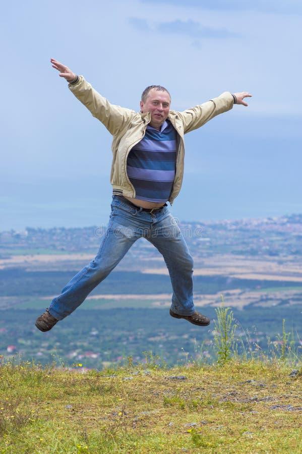 Mens het springen armen en benen op middelbare leeftijd die uit tegen de achtergrond van de mening van de berg worden uitgespreid royalty-vrije stock fotografie