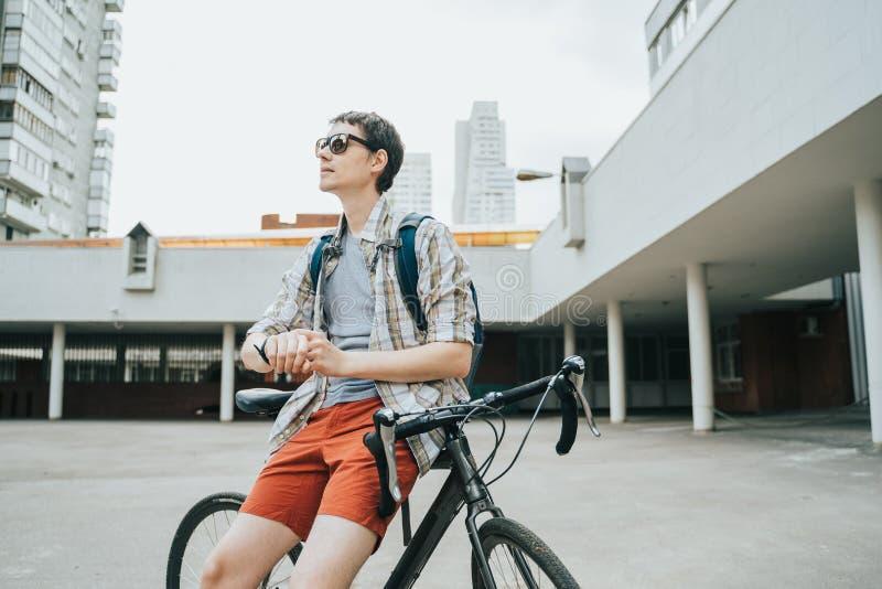 Mens het stellen naast zijn fiets stock foto's