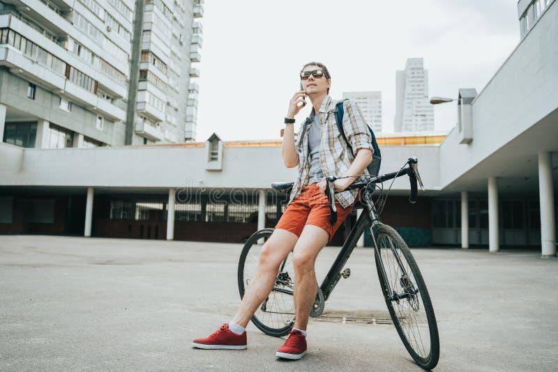 Mens het stellen naast zijn fiets stock fotografie