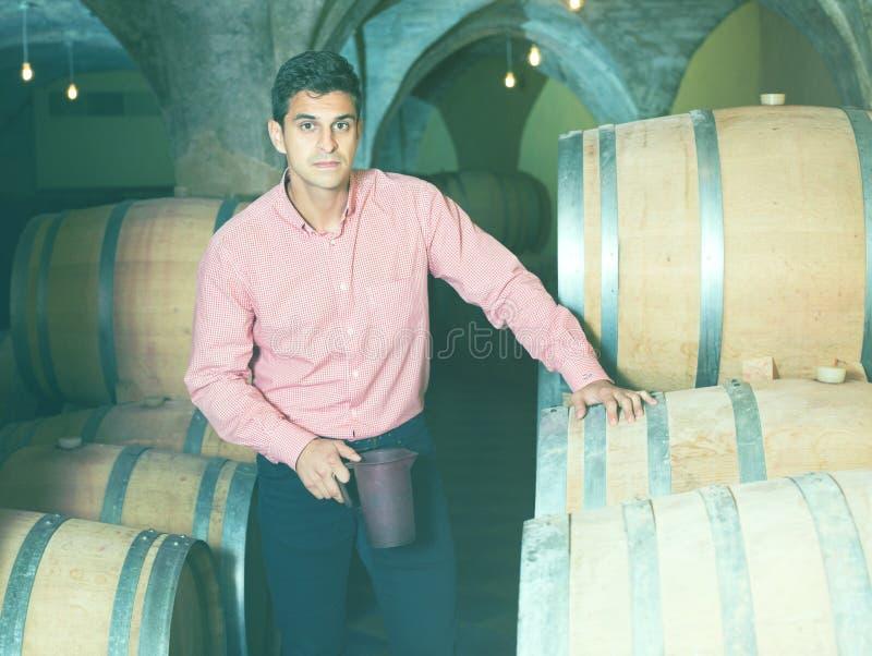 Mens het stellen in wijnmakerijkelder royalty-vrije stock afbeelding