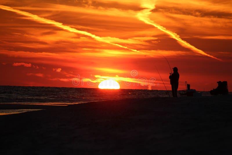 Mens het surfcasting in de zonsondergang in Alabama stock fotografie