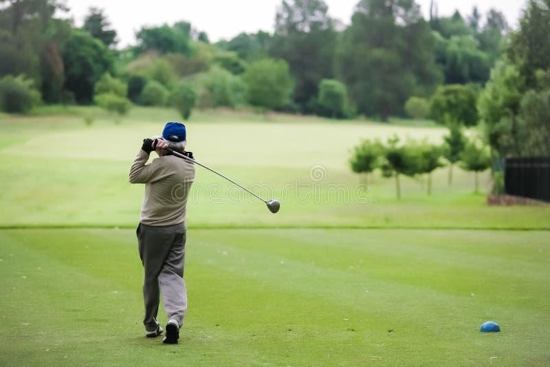 Mens het teeing weg op een golfcursus met een bestuurder royalty-vrije stock afbeeldingen