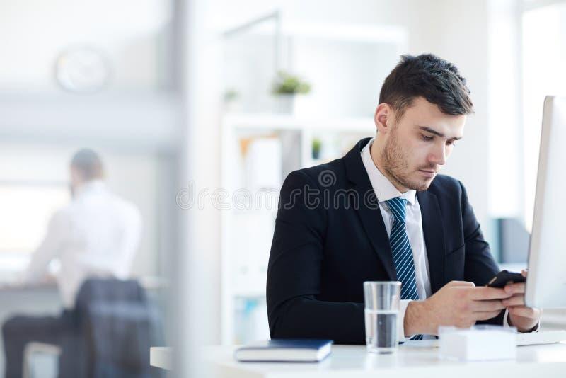 Mens het texting door werkplaats stock afbeelding