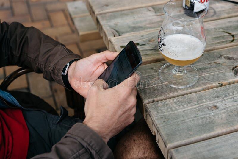 Mens het texting op telefoon terwijl het drinken van bierzitting op een bar royalty-vrije stock afbeeldingen