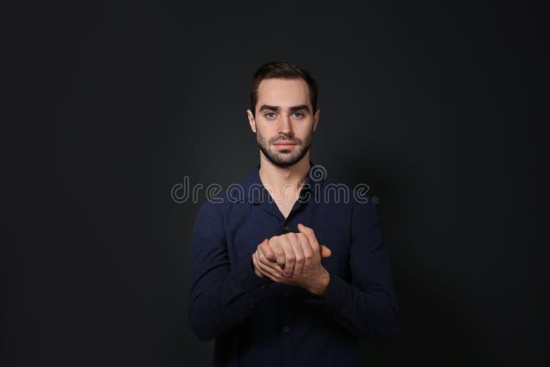 Mens het tonen GELOOFT gebaar in gebarentaal op zwarte royalty-vrije stock afbeelding