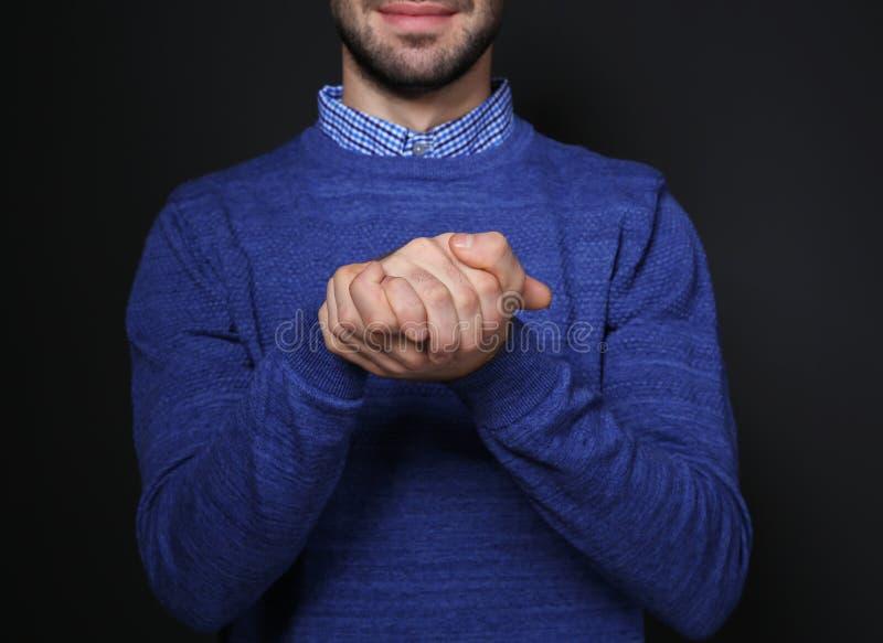 Mens het tonen GELOOFT gebaar in gebarentaal op zwarte, close-up royalty-vrije stock foto