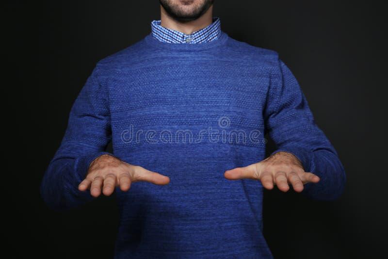 Mens het tonen ZEGENT gebaar in gebarentaal op zwarte achtergrond royalty-vrije stock fotografie