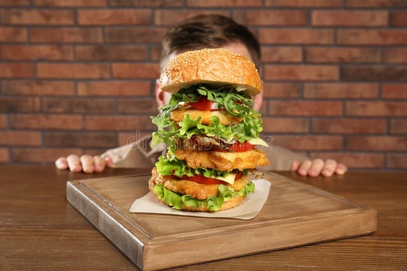 Mens het verbergen achter reusachtige hamburger stock foto's