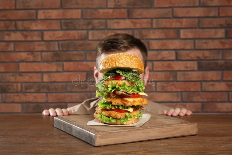 Mens het verbergen achter reusachtige hamburger stock fotografie