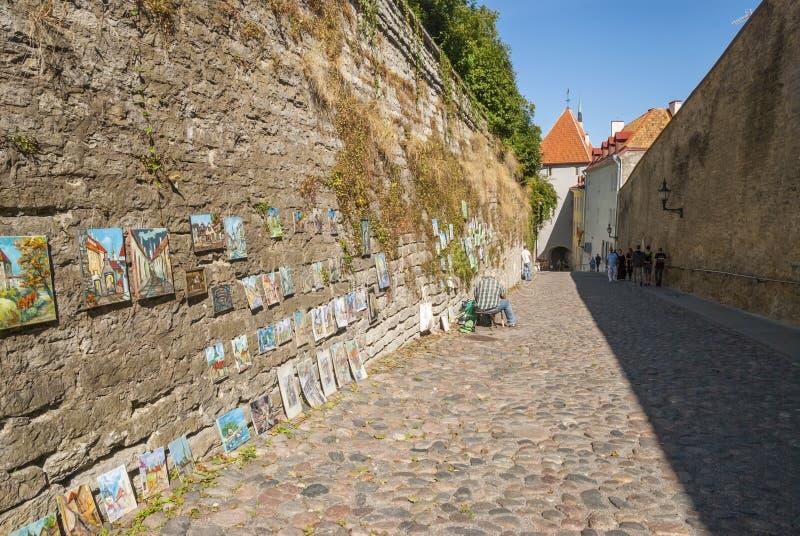 Mens het verkopen paitings in de straat van Tallinn stock foto