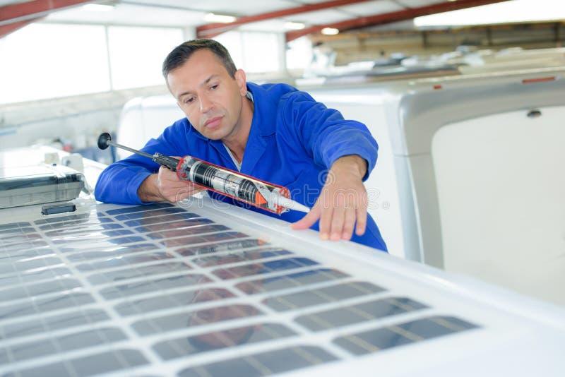 Mens het verzegelen rond zonnepaneel op dakvoertuig stock foto's