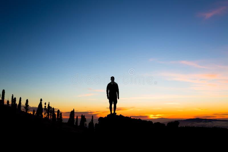 Mens het vieren zonsondergang die mening in bergen bekijken royalty-vrije stock afbeeldingen