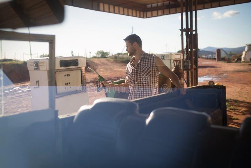 Mens het vullen benzine in auto bij benzinepomp stock afbeeldingen
