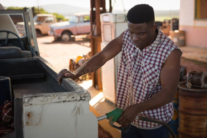 Mens het vullen benzine in auto bij benzinepomp royalty-vrije stock afbeeldingen
