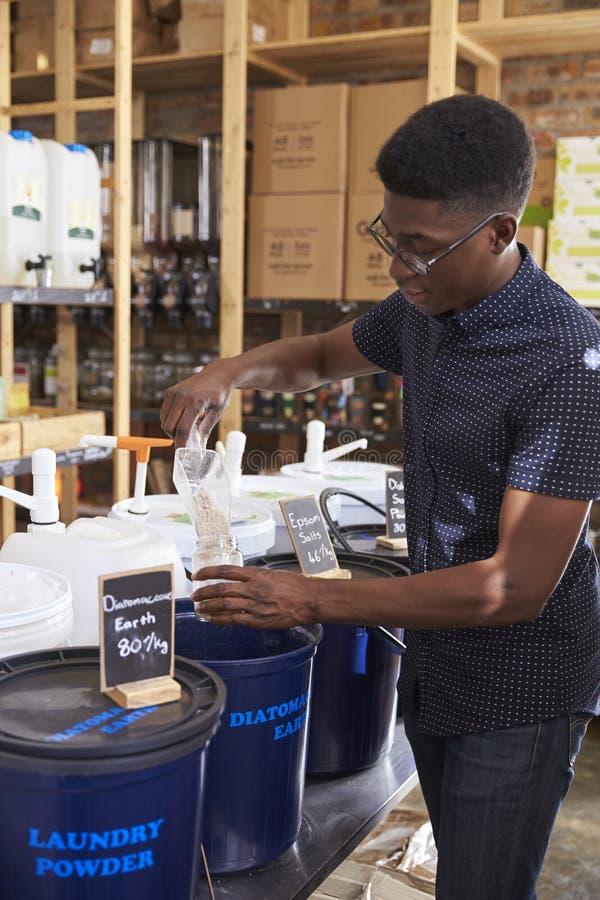 Mens het Vullen Container met Natuurlijke Huisproducten in Plastic Vrije Kruidenierswinkelopslag stock afbeeldingen
