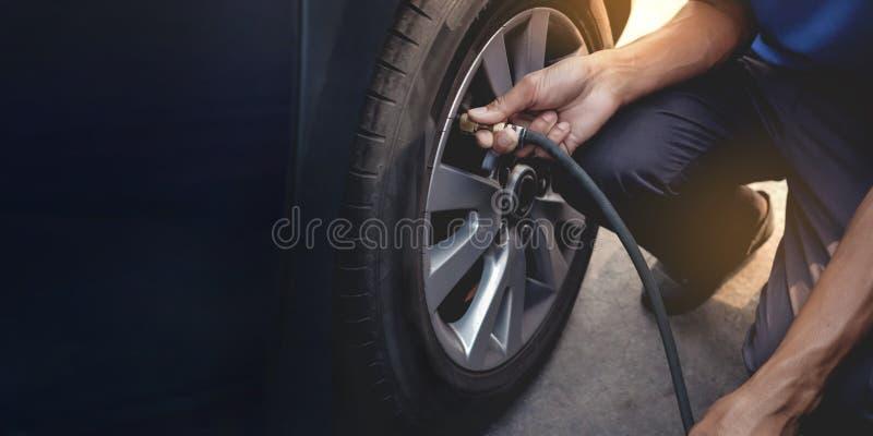 Mens het vullen Lucht in de Band Autobestuurder Checking Air Pressure en Onderhoud zijn Auto zelf stock fotografie