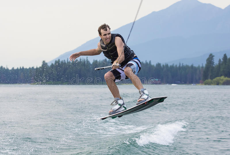 Mens het wakeboarding op een mooi bergmeer royalty-vrije stock fotografie