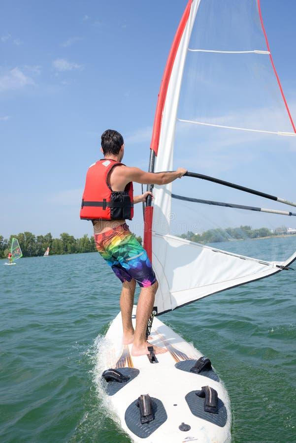 Mens het windsurfing op meer stock foto