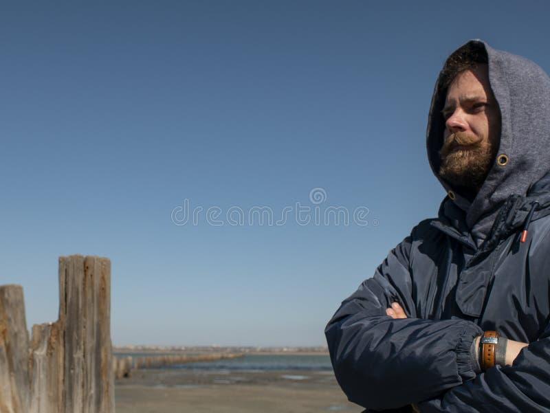 Mens hipster met een baard en een snor in de kap tegen de blauwe hemel en het estuarium royalty-vrije stock foto's