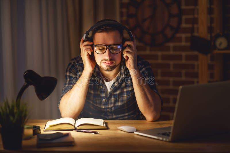 Mens in hoofdtelefoons bij computerhuis in avond in dark stock afbeelding