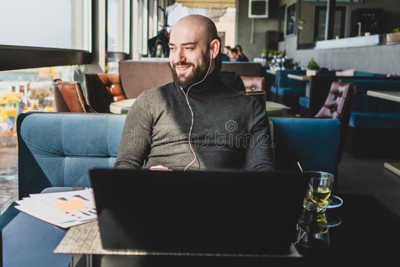 Mens in hoofdtelefoons die aan laptop werken terwijl het zitten in koffie Gebaarde hipster bestudeert online, letten op webinar o royalty-vrije stock foto's