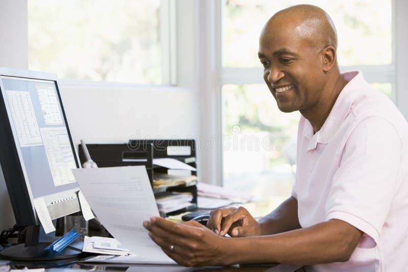 Mens in huisbureau dat computer en het glimlachen gebruikt stock afbeelding