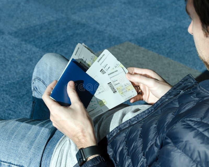 Mens in jeans die bij luchthaven zitten en in de kaartjes en het paspoort van het handenvliegtuig houden stock foto