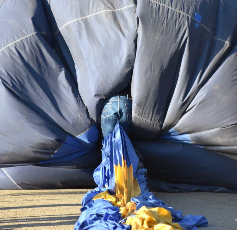 Mens in jeans die een hete luchtballon om het omhoog te verpakken binnensluipen royalty-vrije stock foto's