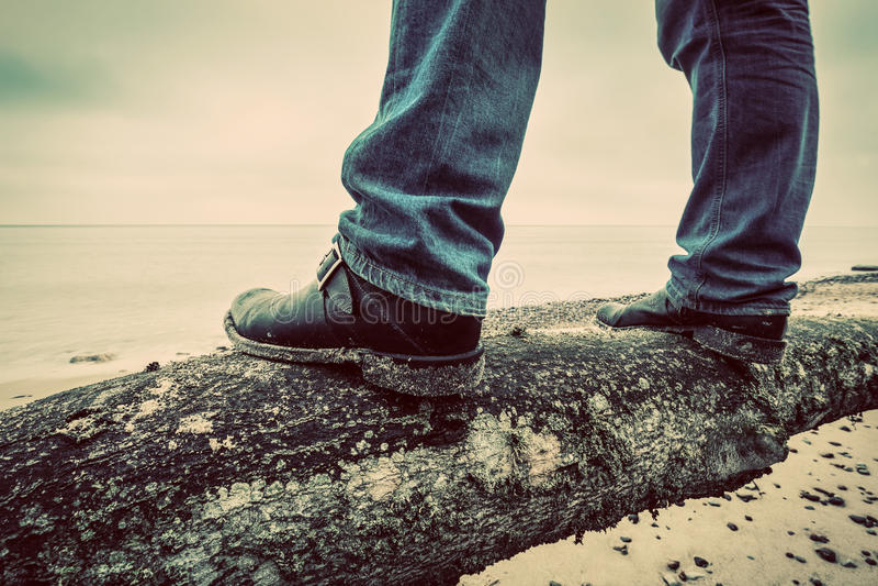 Mens in jeans en elegante schoenen die zich op gevallen boom op wild strand bevinden die op zee kijken wijnoogst stock afbeelding