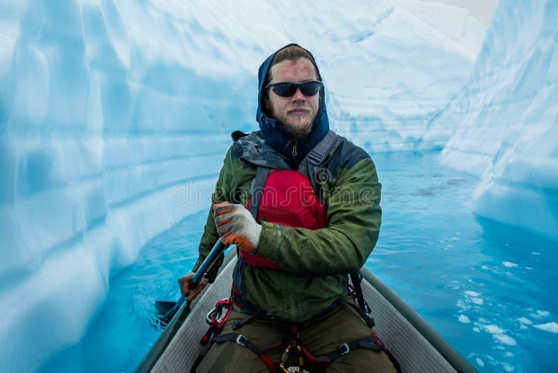 Mens in kano die door smalle ijscanion drijven bovenop een gletsjer in ver Alaska stock afbeeldingen