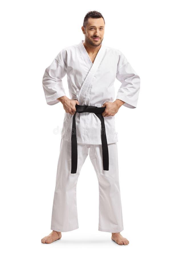 Mens in karatekimono die zijn zwart band houden en bij de camera glimlachen royalty-vrije stock afbeelding