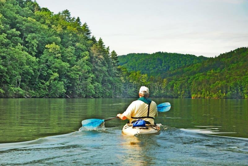 Mens Kayaking op Stil Meer royalty-vrije stock foto's