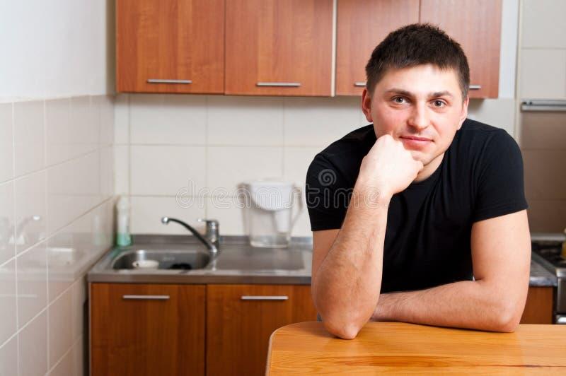 Mens in keuken stock afbeelding