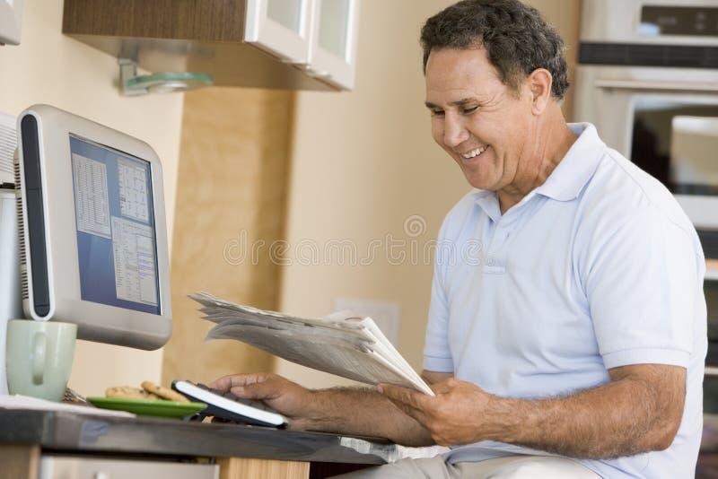Mens in keuken met computer en kranten het glimlachen royalty-vrije stock foto