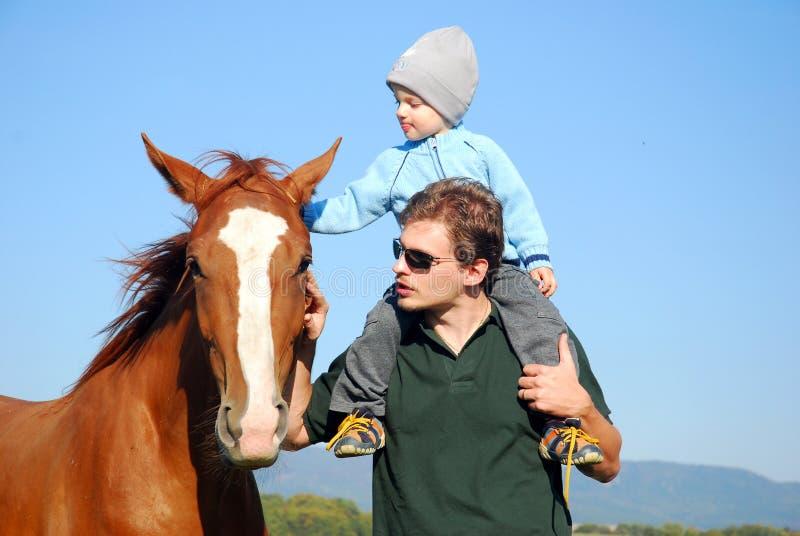 Mens, kind en paard stock afbeeldingen