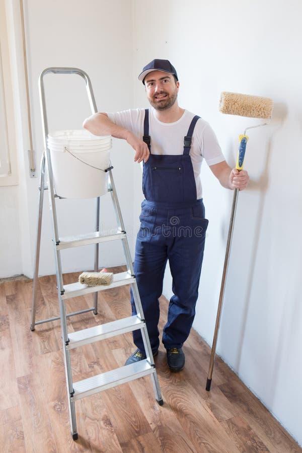 Mens klaar om één muurholding het schilderen hulpmiddelen te schilderen royalty-vrije stock afbeelding