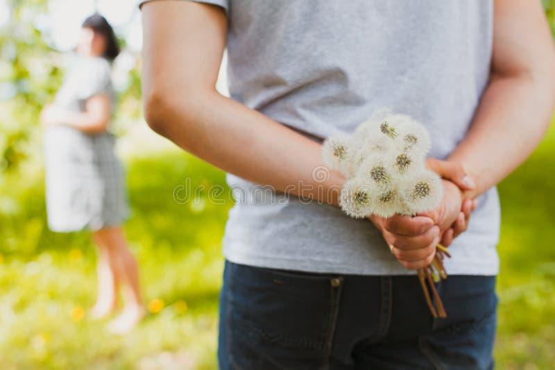 Mens klaar om bloemen aan meisje te geven stock afbeeldingen