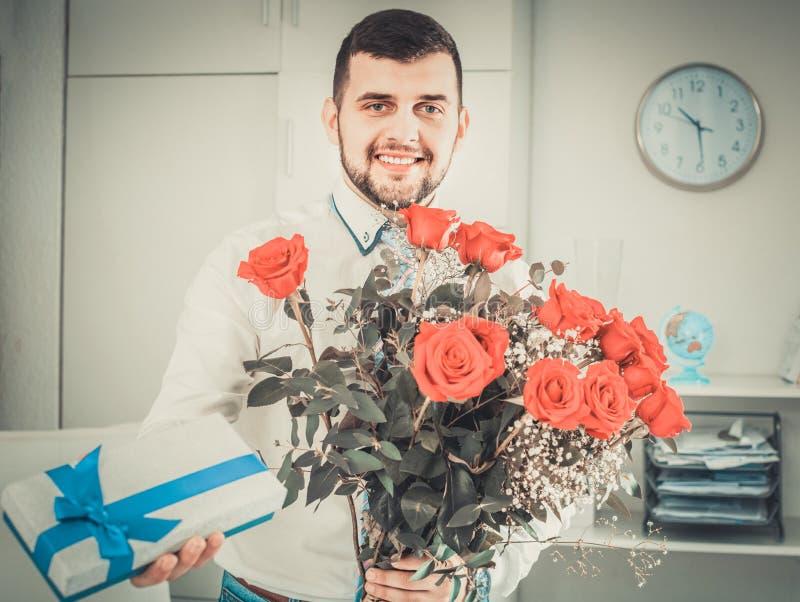 Mens klaar om bloemen en gift bij vakantie voor te stellen stock foto