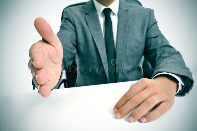 Mens in kostuum die handen aanbieden te schudden royalty-vrije stock fotografie