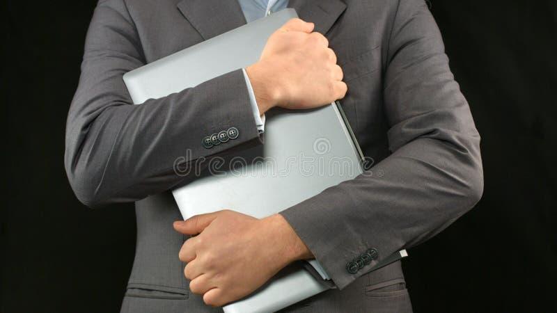 Mens in laptop van de pakholding computer strakke, persoonlijke gegevensbeveiliging royalty-vrije stock fotografie