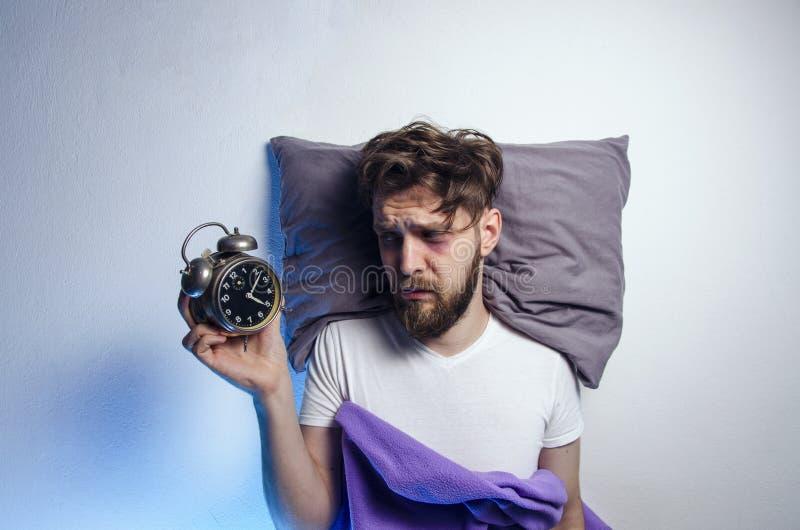 Mens leggen droevig en wakker in bed royalty-vrije stock afbeeldingen