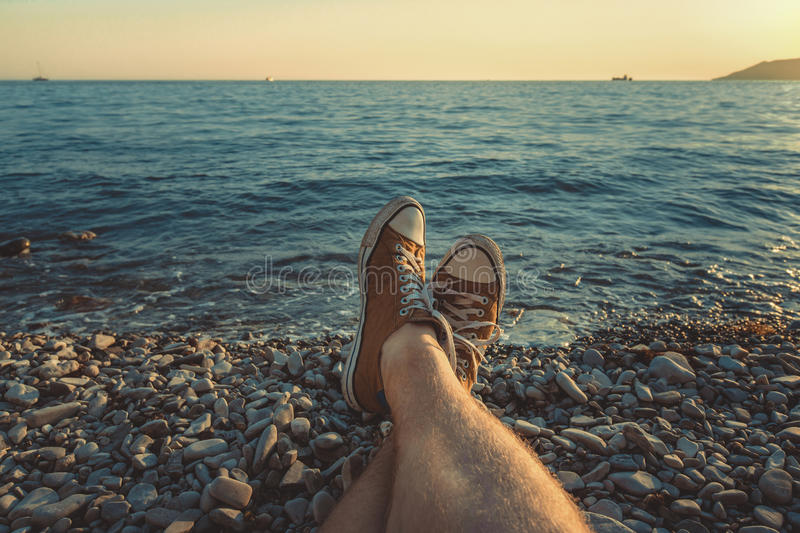 Mens legs in sneakers in background of picturesque sea landscape Summer Beach Relaxing Concept. Beach in summer in Gelendzhik. Mens legs in sneakers in stock images