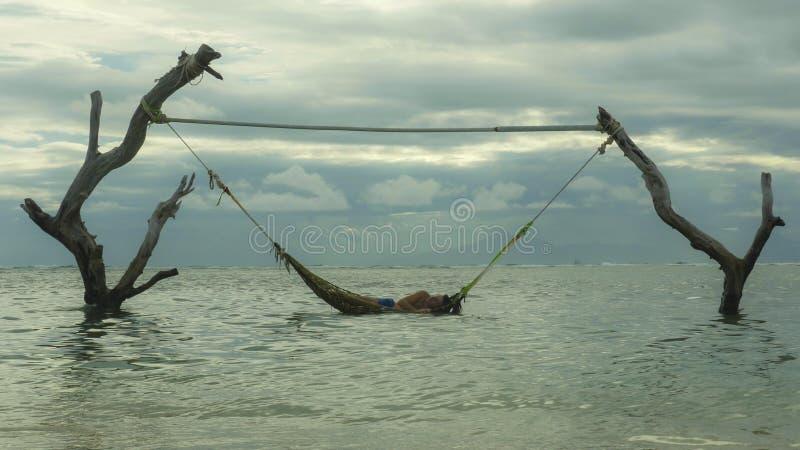 Mens liggen ontspannen en gelukkig in overzeese hangmat verbazende opstelling op boomboomstammen bij tropisch eilandstrand in het stock afbeelding