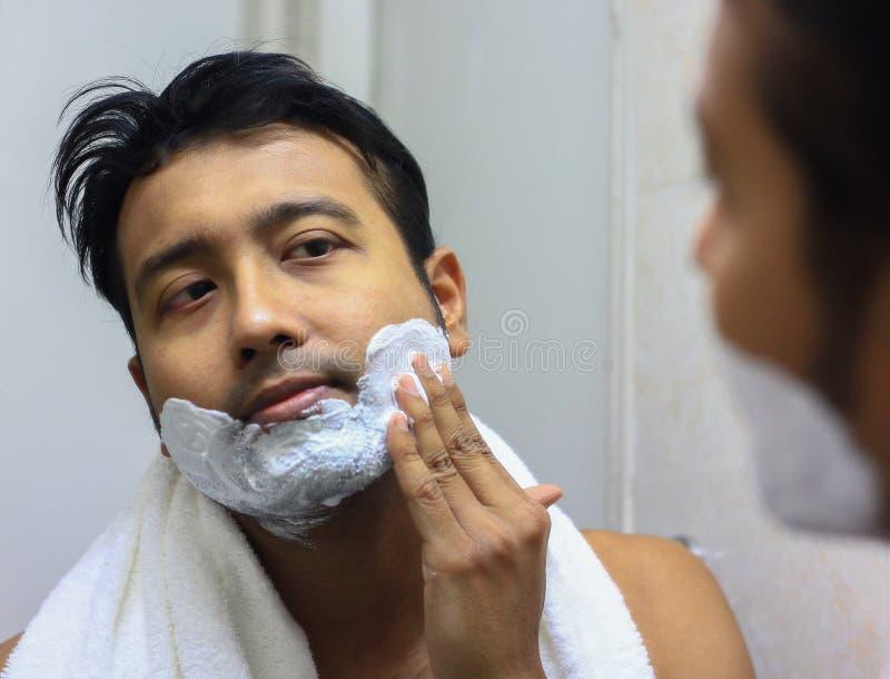 Mens lookingIndian Aziaat na zijn verschijning voor een spiegelschoonheid het stileren levensstijl Het scheren routine die schuim royalty-vrije stock afbeeldingen