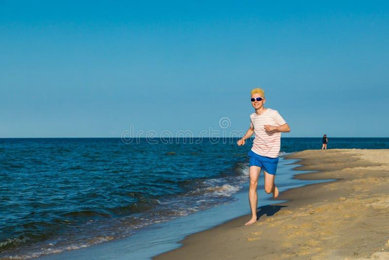 Mens lopen, die op strand springen stock afbeeldingen