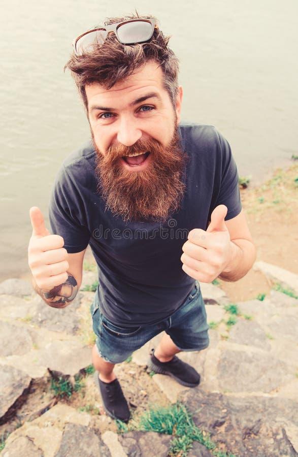 Mens met baard en snor met zonnebril, rivierdijk op achtergrond Hipster op vrolijk gezicht toont duim stock foto's