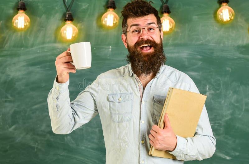 Mens met baard op gelukkig gezicht in klaslokaal De leraar in oogglazen houdt boek en mok koffie of thee Zoete croissant en een k stock afbeelding