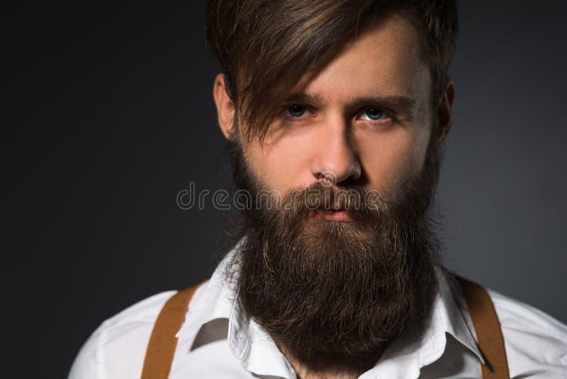 Mens met baard in witte overhemd en bretels stock afbeelding