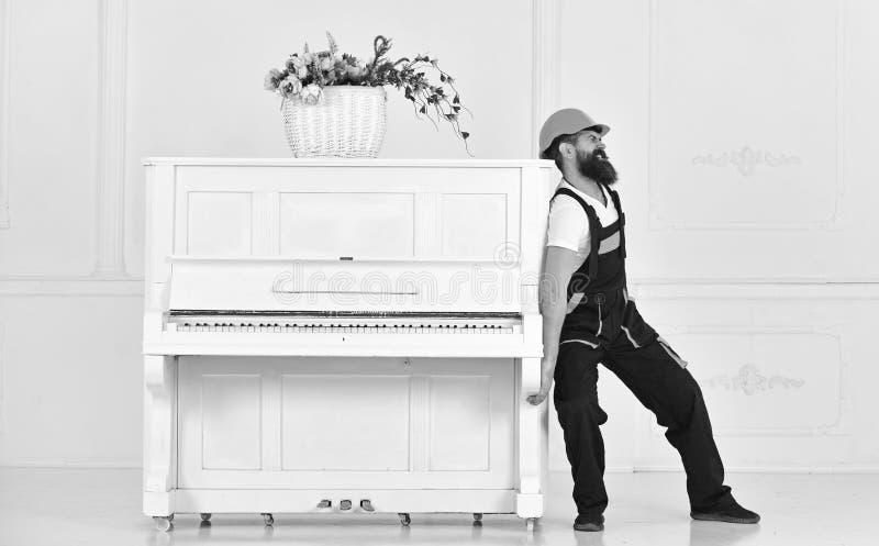 Mens met baardarbeider in helm en overallduwen, inspanningen om piano, witte achtergrond te bewegen De koerier levert meubilair stock afbeelding